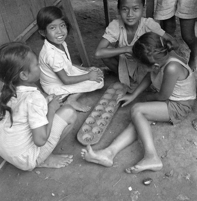 Hayooo, siapa yang masih ingat dengan permainan tradisional ini?. Yap, di beberapa daerah permainan tradisional ini disebut congklak gaes. Dan foto ini diambil tahun 1947. Pasti sekarang anak-anak ini sudah jadi oma semua, Wah, emang deh Pulsker anak Indonesia terkenal akan keceriaan dan keramahannya. Nilai inilah yang harus kita tanamkan kepada adik-adik, sepupu, dan anak kita kelak. Jadi makin bangga nih jadi anak Indonesia.