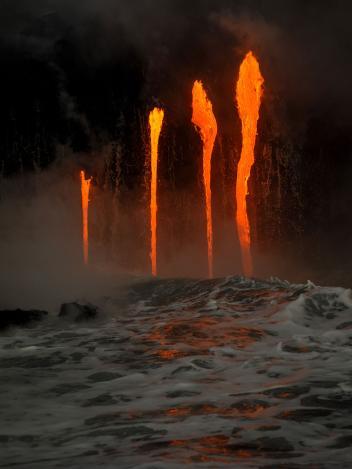 Semburan lava panas di tengah lautan yang keluar dari gunung Kilauea, Hawaii.
