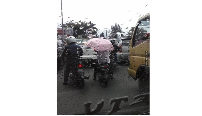 Hanya di Indonesia berkendara saat hujan menggunakan payung.