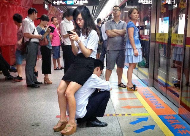 Daripada si pacar harus berdiri lama untuk menunggu kereta, cowok ini bahkan mau menjadi kursi bagi ceweknya.