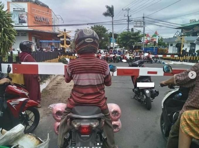 Sambil nunggu kereta lewat, jadi si ibu berdiri aja disana sambil parkir motornya :D