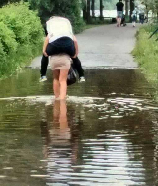 Biasanya cowok yang berkorban buat gendong ceweknya saat banjir, lah ini malah sebaliknya.