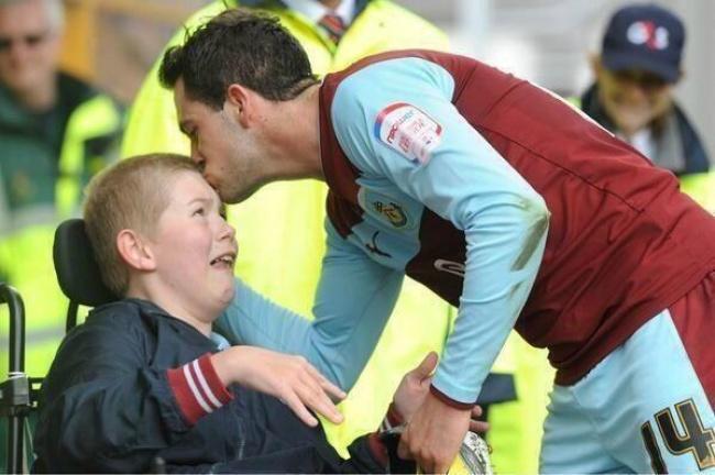 Pemain depan tim Burnley nampak sedang mencium Joseph Skinner, salah satu penonton setia dengan kursi roda. Saking bahagianya, Joseph sampai menitikan air mata lho Pulsker dicium sang idola.