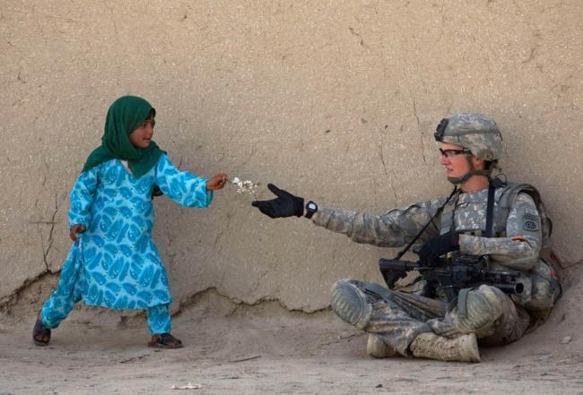 Seolah mengirimkan pesan damai, seorang gadis kecil nampak memberikan sekuntum bunga kepada tentara Amerika di daerah Arghandab, Afghanistan.