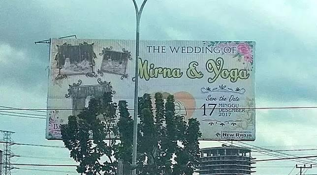 Nggak cukup membuat baliho di depan rumah, pasangan ini juga membuat undangan pernikahan lewat baliho iklan di jalan raya. Kira-kira berapa biayanya ya? Pasti mahal banget deh!