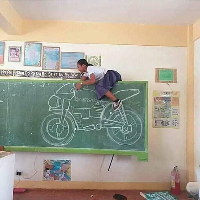 Ada gambar motor besar di papan tulis ini, tapi anehnya bukan siswa laki-laki yang melakukan kekonyolan, melainkan siswa perempuan. Ada-ada saja ya!