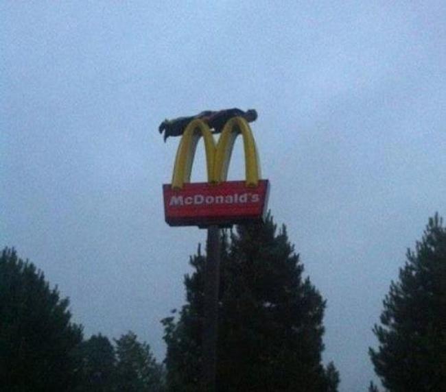 Nggak ada yang ngalahin aksi super gokil pria ini sob. Bayangin aja, dia tidur diatas logo McDonald setinggi itu.