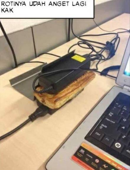 Nggak ada microwave, charger laptop-pun jadi untuk menghangatkan croissant.