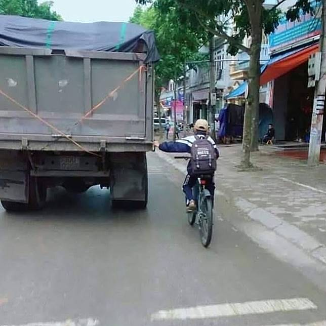 Capek ngayuh sepeda, jadinya pegangan aja ke truk. Jangan dituru ya, ini berbahaya.