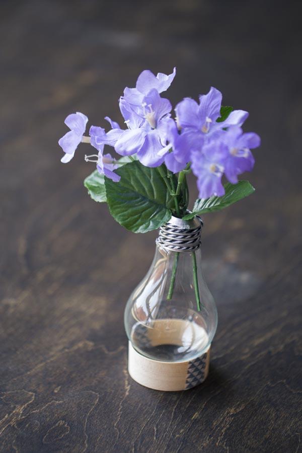 Vas bunga buatan dipajang di meja nan simpel. Gunakan bekas selotip sebagai penyanggahnya.