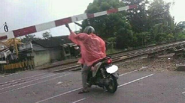 Mungkin karena kebelet, pria yang satu ini rela mempertaruhakn nyawanya dengan membuka palang pintu kereta api.